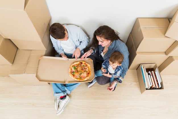 Junge paare mit ihrem sohn, der die pizza in ihrem neuen haus isst Kostenlose Fotos