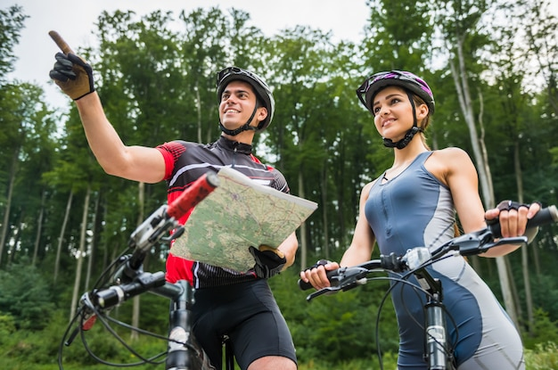 Junge paare mit ihren fahrrädern, die nahe dem wald stehen. Premium Fotos