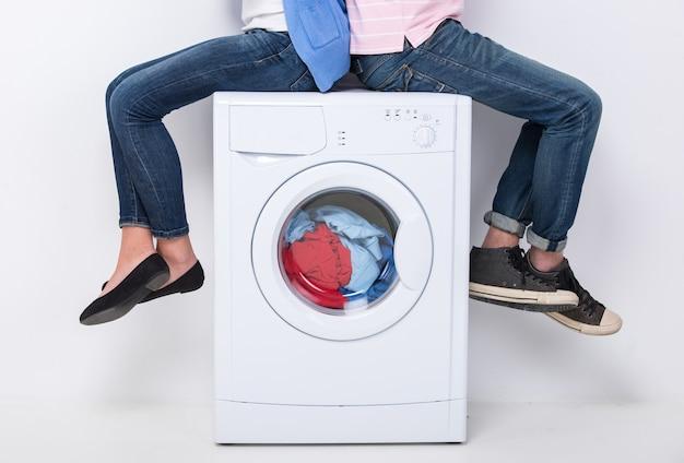 Junge paare sitzen auf der waschmaschine. Premium Fotos