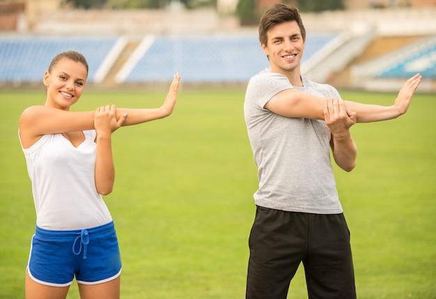 Junge paare tun die übungen und dehnen auf stadion aus. Premium Fotos