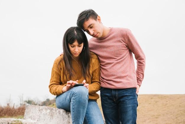 Junge paare unter verwendung des smartphone in der natur Kostenlose Fotos