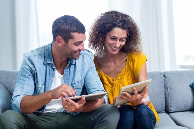 Junge paare unter verwendung einer digitalen tablette auf sofa Premium Fotos