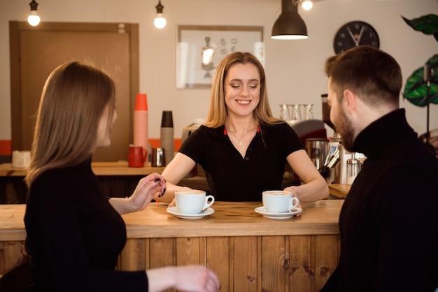 Junge paare von den kunden, die kaffee vom barista in der kaffeestube nehmen. Premium Fotos