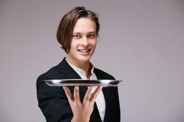 Junge person in einem anzug, der ein leeres tablett lokalisiert auf weißer wand hält Kostenlose Fotos