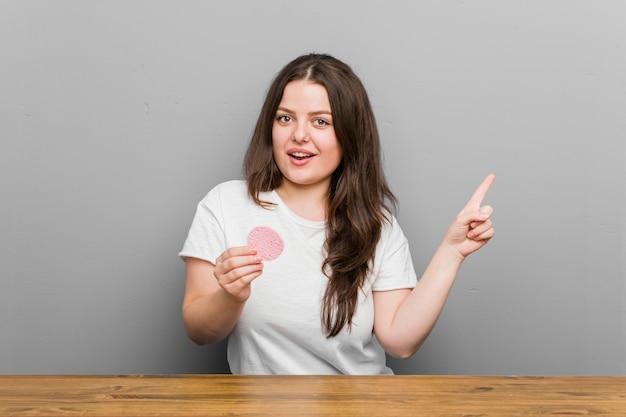 Junge plus die curvy frau der größe, die einen gesichtsschwamm lächelt hält, freundlich zeigend mit dem zeigefinger weg. Premium Fotos
