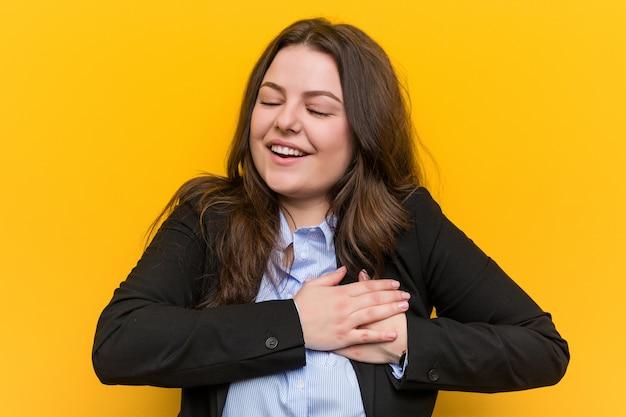Junge plus die kaukasische geschäftsfrau der größe, die hände auf herzen, des glückes halten lacht. Premium Fotos