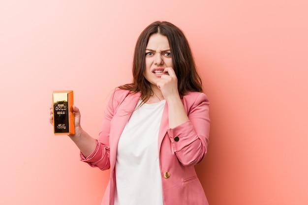 Junge plus die kurvige geschäftsfrau der größe, die beißende fingernägel eines goldbarrens, nervös und sehr besorgt hält Premium Fotos