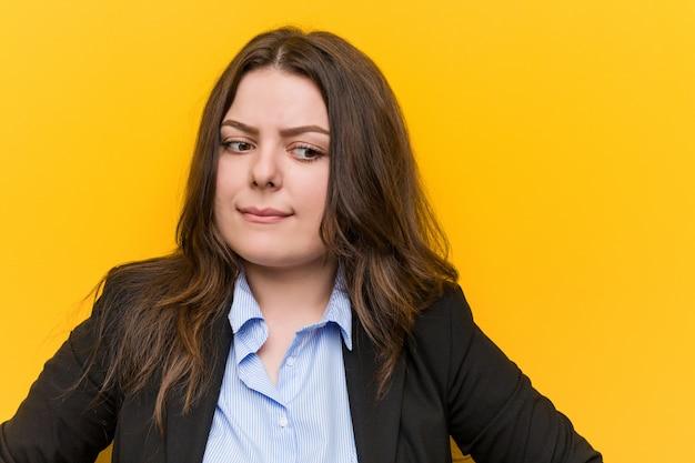 Junge plus größe kaukasische geschäftsfrau verwirrt, fühlt sich zweifelhaft und unsicher. Premium Fotos