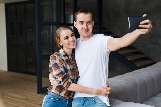 Junge positive paare, die zu hause selfie im raum nehmen Kostenlose Fotos