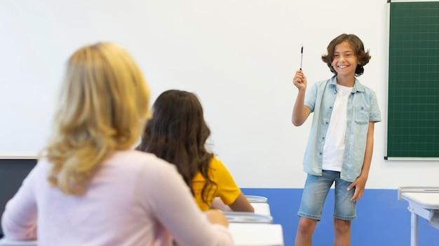 Junge präsentiert vor der klasse Kostenlose Fotos