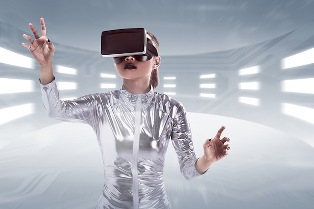 Junge recht asiatische frau, die vr-kopfhörer innerhalb der virtuellen welt trägt Premium Fotos