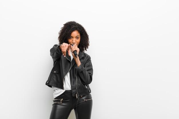 Junge recht schwarze frau mit einem mikrofon, das eine lederjacke gegen weiße wand trägt Premium Fotos
