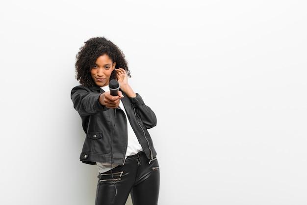 Junge recht schwarze frau mit einem mikrofon, das eine lederjackeweißwand trägt Premium Fotos