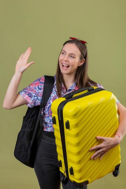 Junge reisende frau, die rote sonnenbrille auf kopf steht, der mit rucksack hält, der koffer hält, der ihre hand während des begrüßens oder der abschiedsgeste lächelt, die mit glücklichem gesicht über lokalisiertem grün lächelt Kostenlose Fotos