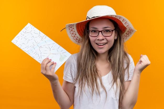 Junge reisende frau im weißen t-shirt, das sommerhut hält, der karte zusammenballt faust aufgeregt und glücklich lächelnd steht über orange wand Kostenlose Fotos