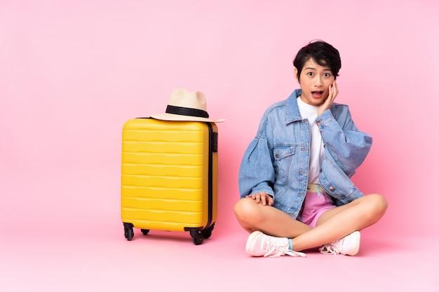 Junge reisende vietnamesische frau mit koffer, der auf dem boden über rosa wand mit überraschtem und schockiertem gesichtsausdruck sitzt Premium Fotos