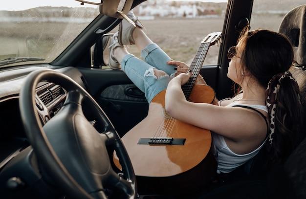 Junge reisendfrau, welche die gitarre innerhalb des jeepautos macht wanderlustferien bei sonnenuntergang im sommer spielt Premium Fotos