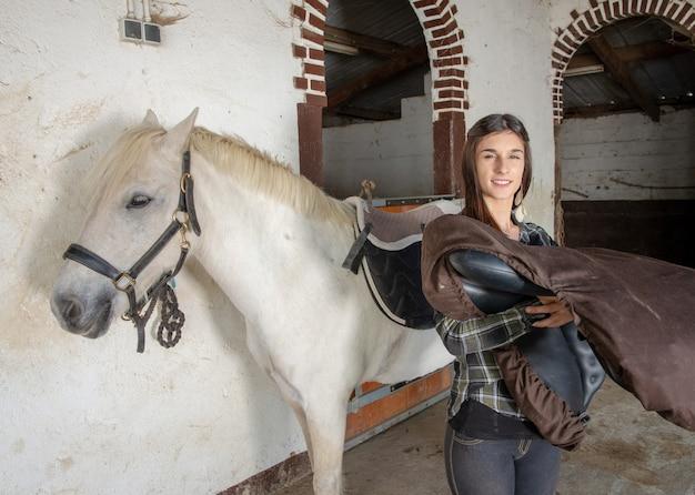 Junge reiterfrau mit schimmel Premium Fotos