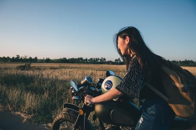 Junge reizvolle frau auf einem motorrad in der natur auf dem sonnenuntergang. reisekonzept. Premium Fotos