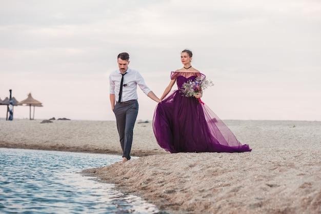 Junge romantische paare, die auf dem strand von meer laufen Kostenlose Fotos