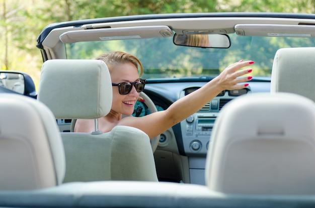 Junge rote frau, die ihre freunde beim fahren begrüßt Premium Fotos
