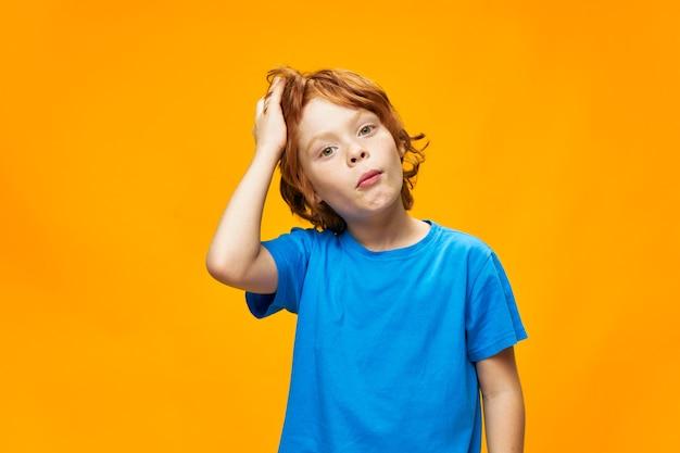 Junge rote haare blaues t-shirt gelb isolierte sommersprossen und überraschter blick benommen blick Premium Fotos
