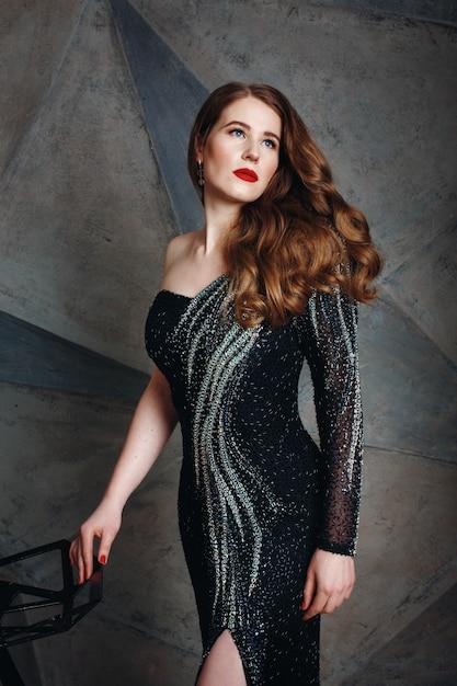 Junge rote haarfrau im schwarzen luxuskleid Premium Fotos
