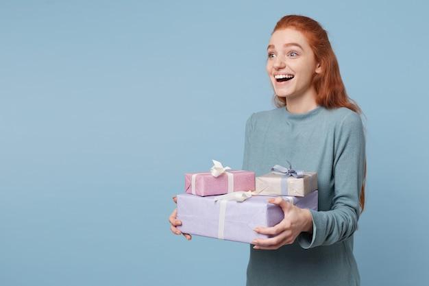 Junge rothaarige frau, die seitlich steht und abstand hält, der kisten mit geschenken hält Kostenlose Fotos
