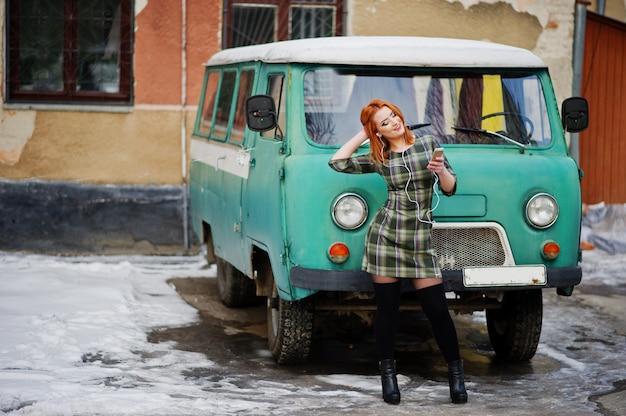 Junge rothaarige frauendame mit dem handy und kopfhörern, tragend auf überprüftem kleid im alten weinleseminivanbus. Premium Fotos