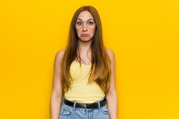 Junge rothaarige ingwerfrau mit sommersprossigen achselzucken und offenen augen verwirrt. Premium Fotos
