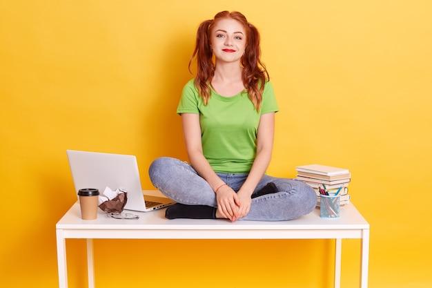 Junge rothaarige studentin, die auf weißem tisch mit gekreuzten beinen sitzt, lustige dame mit pferdeschwänzen studiert, kamera betrachtend Kostenlose Fotos