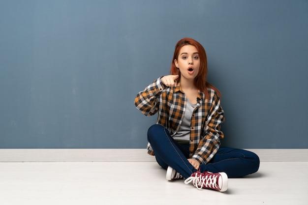 Junge rothaarigefrau, die auf dem boden überrascht sitzt und front zeigt Premium Fotos