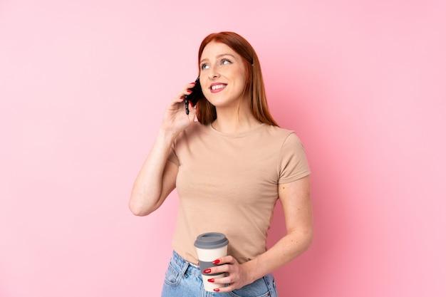 Junge rothaarigefrau, die kaffee hält, um und ein mobile wegzunehmen Premium Fotos