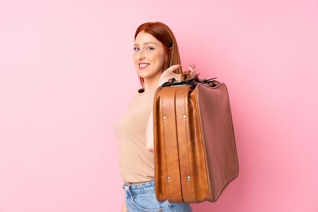 Junge rothaarigefrau über dem lokalisierten rosa hintergrund, der einen weinleseaktenkoffer hält Premium Fotos