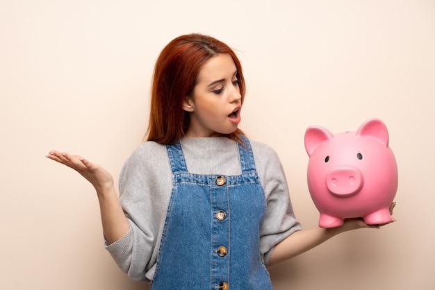 Junge rothaarigefrau über lokalisiertem überrascht beim halten eines sparschweins Premium Fotos