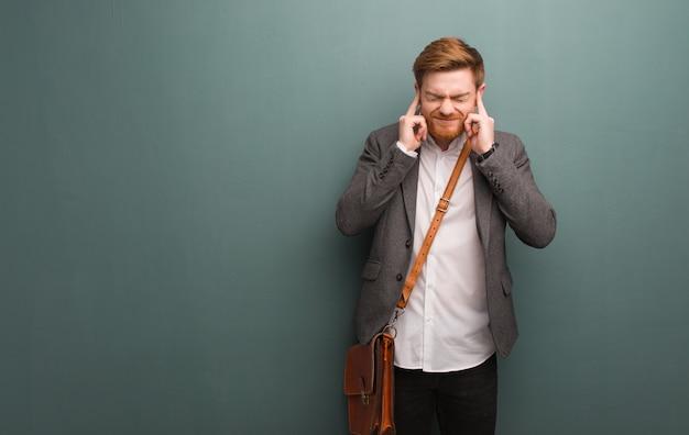Junge rothaarigegeschäftsmann-bedeckungsohren mit den händen Premium Fotos