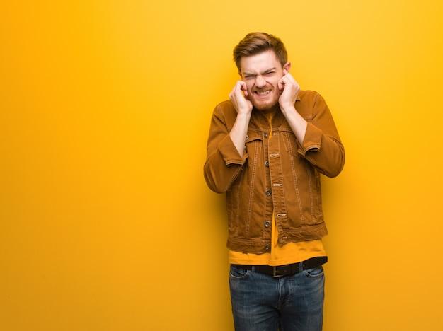 Junge rothaarigemann-bedeckungsohren mit den händen Premium Fotos