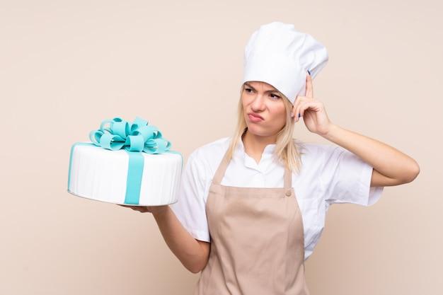 Junge russische frau mit einem großen kuchen über
