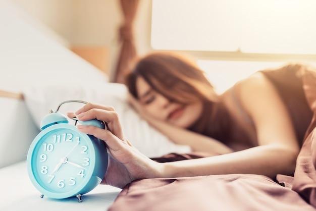 Junge schlafende frau der nahaufnahme und aufstiegshand, zum des weckers im schlafzimmer zu hause auszuschalten Premium Fotos