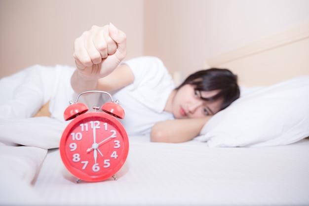 Junge schlafende frau und wecker im schlafzimmer zu hause Kostenlose Fotos