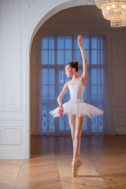 Junge schlanke ballerina in einem weißen tutu tanzt auf spitzenschuhen in einem geräumigen, hellen raum mit großen fenstern. Premium Fotos