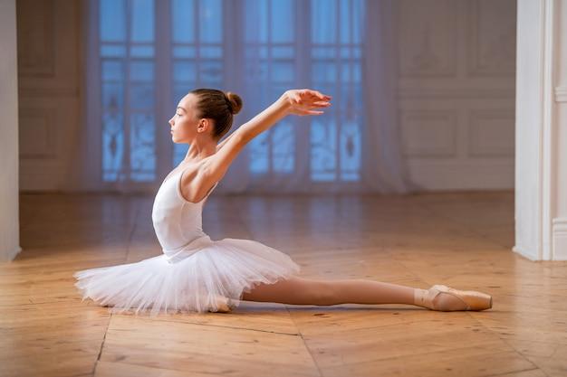 Junge schlanke ballerina in einem weißen tutu tanzt einen schwan auf spitzenschuhen in einem geräumigen hellen raum Premium Fotos