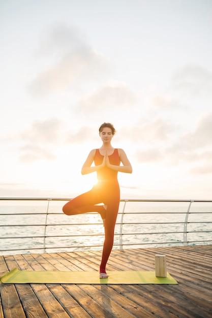 Junge schlanke schöne attraktive frau, die yoga am morgen auf sonnenaufgang durch meer, gesunden lebensstil tut Kostenlose Fotos