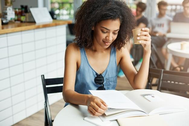 Junge schöne afrikanische studentin, die lächelnd im café sitzt und die zeitschrift beim kaffeetrinken betrachtet. lernen und bildung. Kostenlose Fotos