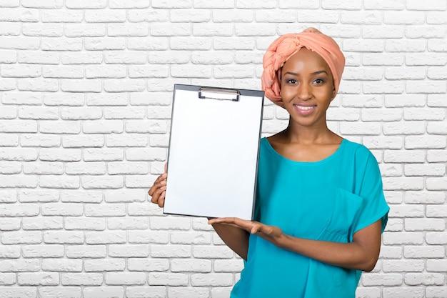 Junge schöne afroamerikanerfrau, die klemmbrett zeigt Premium Fotos