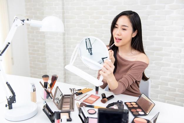 Junge schöne asiatin, die make-uptutorial tut Premium Fotos