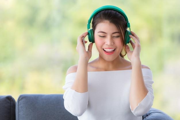 Junge schöne asiatische frau, die auf sofa sitzt und musik mit kopfhörer in der entspannung hört. Premium Fotos