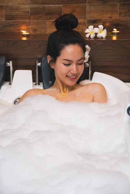 Junge schöne asien-frau nimmt schaumbad Premium Fotos