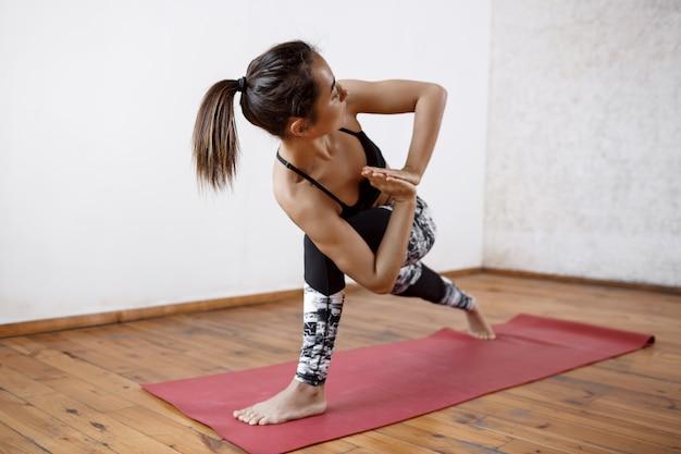 Junge schöne athletische frau, die innenyoga auf roter matte praktiziert Kostenlose Fotos