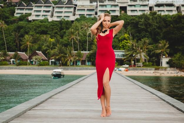 Junge schöne attraktive frau, die allein auf pier im luxusresorthotel, sommerferien, rotes langes kleid, blondes haar, sexy kleidung, tropischer strand, verführerisch, sinnlich, lächelnd steht Kostenlose Fotos